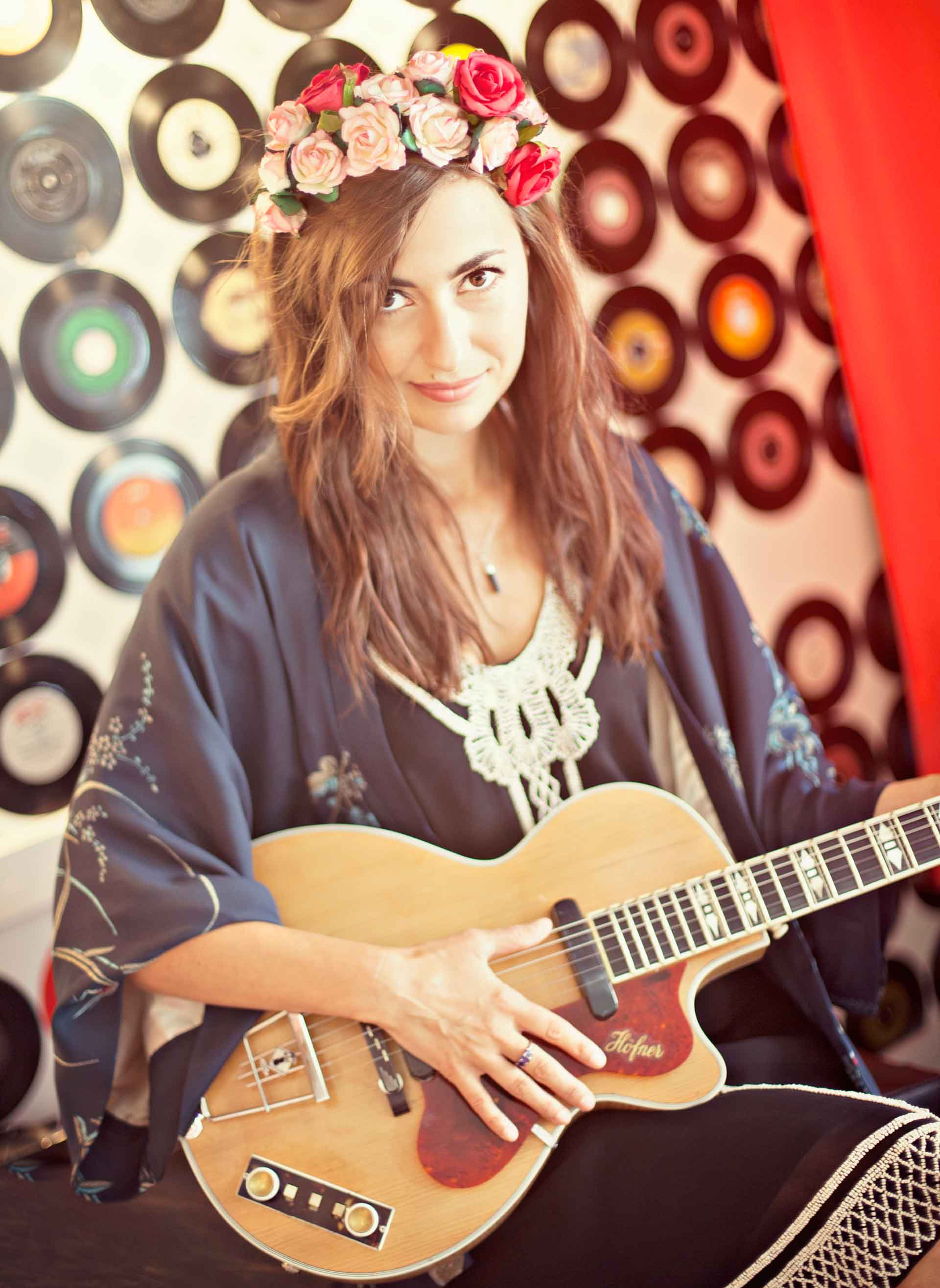 Picture of Manchester musician Zoe Kyoti with flowers in her hair holding a guitar. Copyright Zoe Kyoti - Official Site