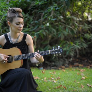 Image showing musician Zoe Kyoti playing guitar in a park. Copyright Zoe Kyoti - Official Site
