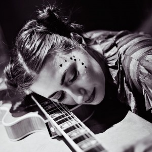 Black and white image - Manchester singer-songwriter with head on guitar - Zoe Kyoti - Copyright Zoe Kyoti - Official Site