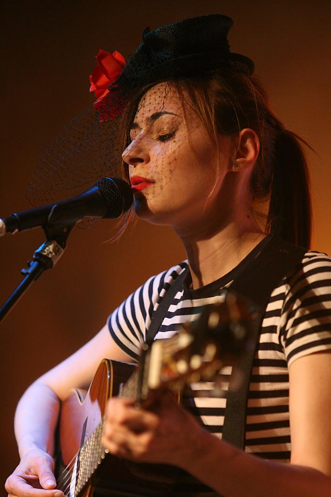Image of Manchester UK based singer-songwriter Zoe Kyoti singing and playing an acoustic guitar. Copyright Zoe Kyoti - Official Site